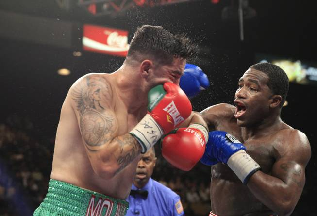 Carlos Molina of the U.S. takes a punch from Adrien Broner, also of the U.S., during their super lightweight fight at the MGM Grand Garden Arena on Saturday, May 3, 2014.