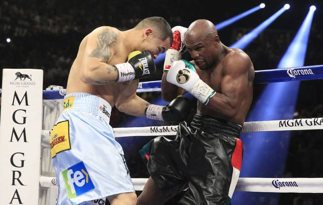 Marcos Maidana, left, of Argentina battles it out with Floyd Mayweather Jr. of the U.S. during their WBC/WBA welterweight unification fight at the MGM Grand Garden Arena on Saturday, May 3, 2014.
