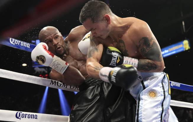 Floyd Mayweather Jr. of the U.S. avoids a punch from Marcos Maidana of Argentina during their WBC/WBA welterweight unification fight at the MGM Grand Garden Arena on Saturday, May 3, 2014.