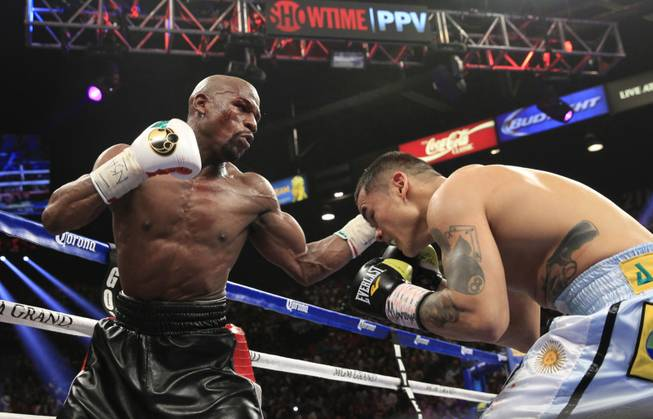 Floyd Mayweather Jr. of the U.S. punches at Marcos Maidana of Argentina during their WBC/WBA welterweight unification fight at the MGM Grand Garden Arena on Saturday, May 3, 2014.