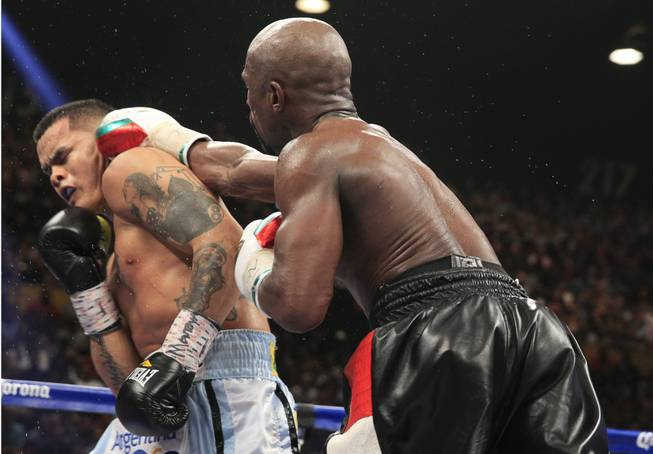 Marcos Maidana, left, of Argentina is punched by Floyd Mayweather Jr. of the U.S. during their WBC/WBA welterweight unification fight at the MGM Grand Garden Arena on Saturday, May 3, 2014.