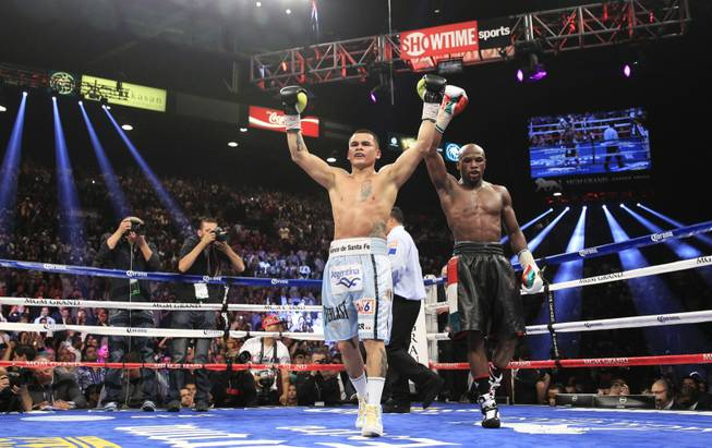Marcos Maidana, left, of Argentina and Floyd Mayweather Jr. of the U.S. both celebrate after their WBC/WBA welterweight unification fight at the MGM Grand Garden Arena on Saturday, May 3, 2014.