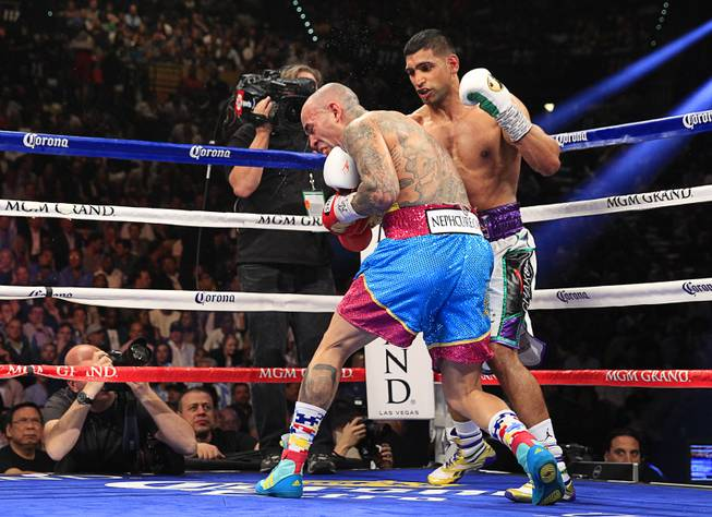 Amir Khan (R) of Britain connects with a punch that knocks down Luis Collazo during their welterweight fight at the MGM Grand Garden Arena Saturday, May 3, 2014.