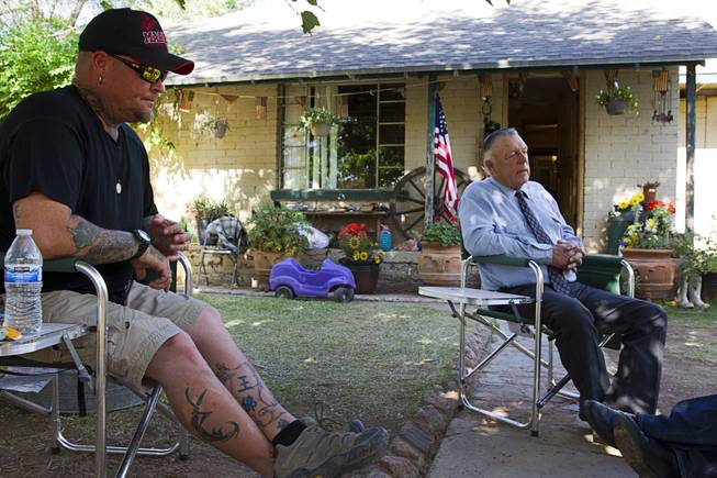 Booda (no last name provided) of Prescott, Ariz. sits by rancher Cliven Bundy during an interview at the Bundy ranch house near Bunkerville, Sunday, May 4, 2014.
