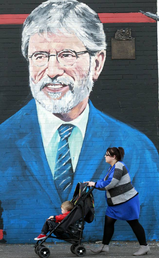 A woman and child make their way past a newly painted mural of Gerry Adams on the Falls Road, West Belfast, Northern Ireland, Friday, May, 2, 2014. Police continue to question the Sinn Fein leader Gerry Adams at Antrim police station about the 1972 murder of Jean McConville.
