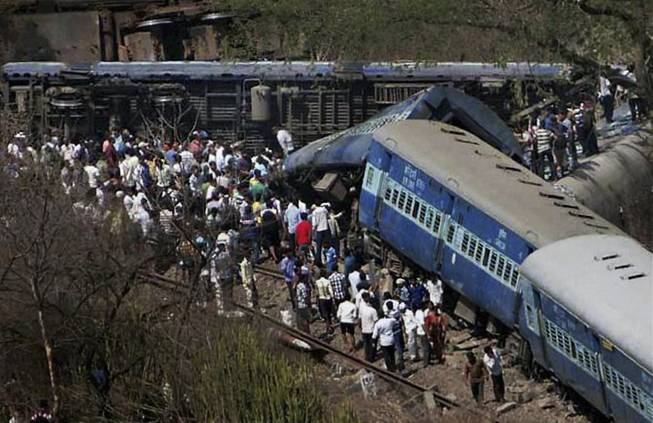 People gather around a passenger train that derailed near Roha station, 110 kilometers (70 miles) south of Mumbai, Maharashtra state, India, Sunday, May 4, 2014. The cause of the accident was not immediately known.