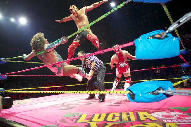 In this Feb. 12, 2014, photo, wrestler Niebla Roja, top, flies over referee Platainitos, to land on wrestler Cassandro, left, during a performance at Lucha VaVoom's Valentine's show at The Mayan Theatre downtown Los Angeles. At right, wrestler, Dr. Maldad. The esoteric hybrid of American burlesque and Mexican wrestling is an outrageous hit.
