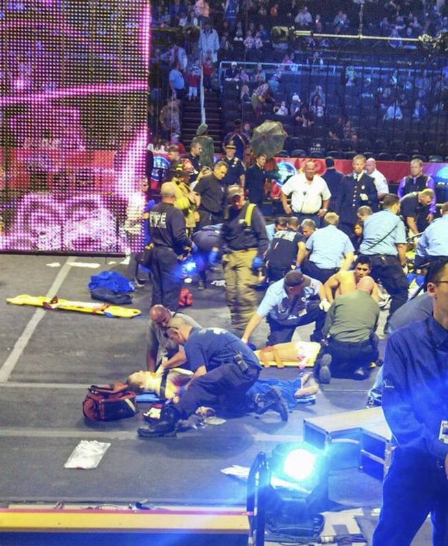 In this photo provided by Rose Viveiros, first responders work at the center ring after a platform collapsed during an aerial hair-hanging stunt at the Ringling Brothers and Barnum and Bailey Circus, Sunday, May 4, 2014, in Providence, R.I. At least nine performers were seriously injured in the fall, including a dancer below, while an unknown number of others suffered minor injuries.