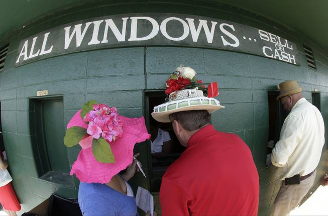 Fans make wagers before the 140th running of the Kentucky Derby horse race at Churchill Downs Saturday, May 3, 2014, in Louisville, Ky.