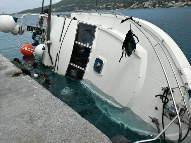 In this photo released by the Hellenic Coast Guard, divers search a yacht used to transport immigrants illegally that overturned in a fatal accident at the port of Vathy on the Greek island of Samos, on Monday, May 5, 2014.