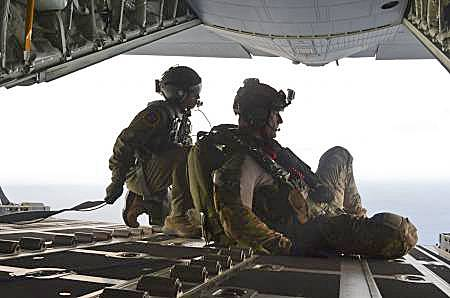 In this May 3, 2014, image provided by the U.S. Air Force, Airman 1st Class Franscisco Harper, left, and a pararescue Airman survey the area as U.S. Air Force pararescue forces parachute into the Pacific Ocean to aid to two critically injured sailors aboard a Venezuelan fishing boat.