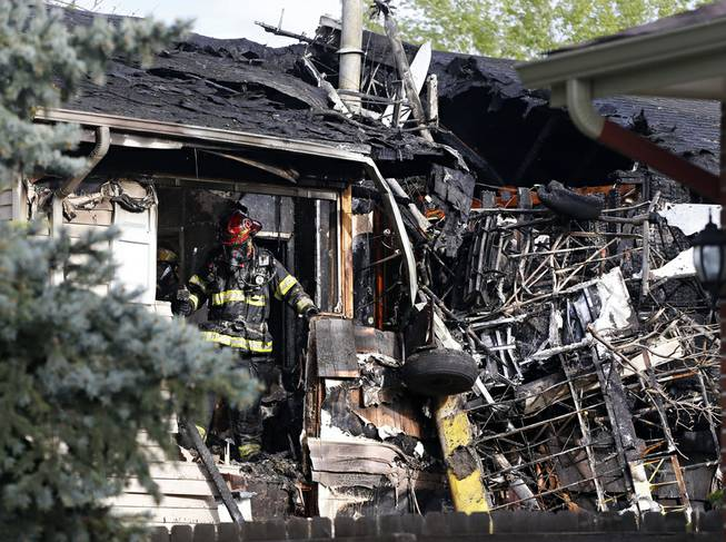 A firefighter looks for hotspots in the debris after his team put out a fire at the scene where a small plane crashed into a home in Northglenn, Colo., Monday, May 5, 2014.