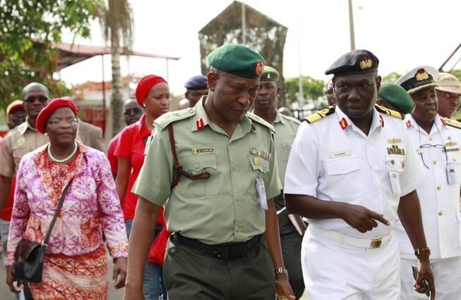 Brig. Gen. Chris Olukolade, Nigeria's top military spokesman, centre, walks with representatives of  kidnapped schoolgirls of Chibok secondary school, for a meeting at the defense  headquarters, in Abuja, Nigeria, Tuesday, May 6, 2014.