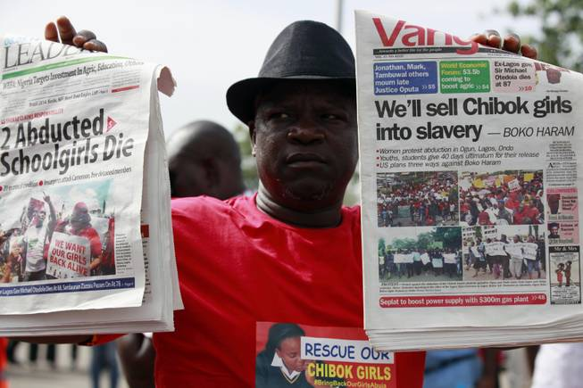 A man display copies of local newspapers during a demonstration calling on the government to rescue kidnapped school girls from Chibok government secondary school, outside the defense  headquarters, in Abuja, Nigeria, Tuesday, May 6, 2014.