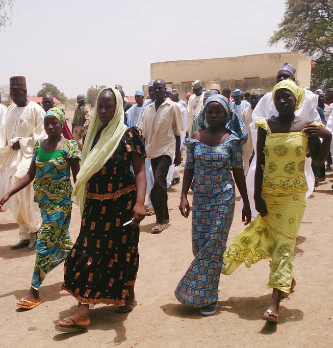 In this Monday April 21, 2014 file photo, four female students of government secondary school Chibok, who were abducted by gunmen and reunited with their families walk in Chibok, Nigeria.