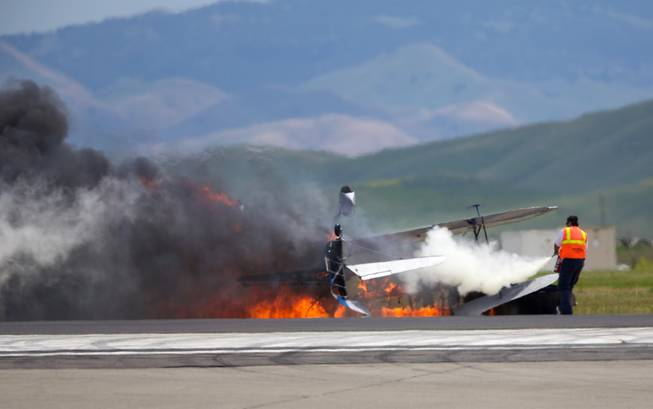 A worker fights a fire after a vintage biplane crashed upside down on a runway at an air show at Travis Air Force Base in Fairfield, Calif., Sunday, May 4, 2014. The pilot, Edward Andreini, 77, of Half Moon Bay, was killed when the plane, flying low over the tarmac, crashed and caught fire.