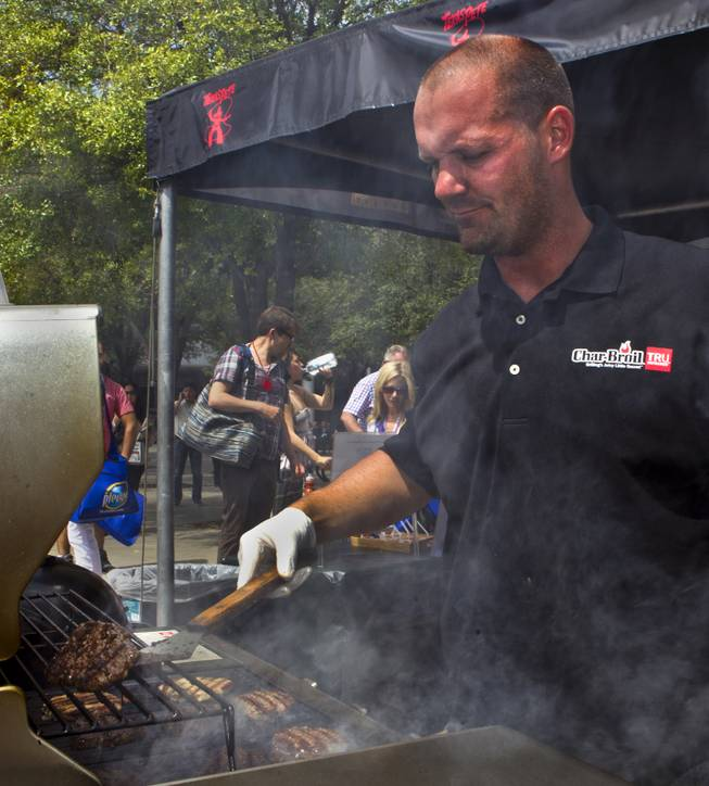 Michael Orth of Jacksonville, Fl., grills up another batch of burgers at the Char-Broil display during the National Hardware Show 2014 outside the Las Vegas Convention Center on Wednesday, May 7, 2014.   L.E. Baskow