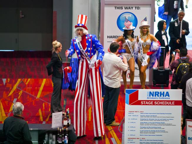 An Uncle Sam on stilts passes out necklaces to attendees about an entrance to the National Hardware Show 2014 in the Las Vegas Convention Center on Wednesday, May 7, 2014.   L.E. Baskow