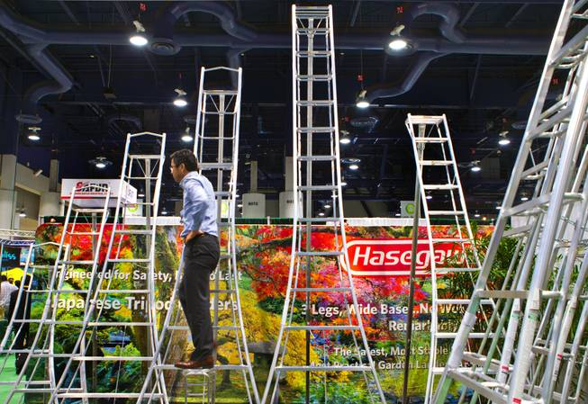 Kinya Osaka displays a series of Hasegawa ladders during the National Hardware Show 2014 in the Las Vegas Convention Center on Wednesday, May 7, 2014.   L.E. Baskow