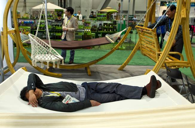 A representative of Xuzhou Lijun Crafts, Co., LTD., takes a nap on one of their hammocks on display at the National Hardware Show 2014 in the Las Vegas Convention Center on Wednesday, May 7, 2014.   L.E. Baskow