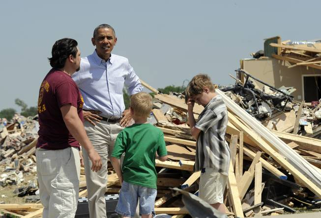President Barack Obama tours tornado-damaged areas of Vilonia, Ark., Wednesday, May 7, 2014, and talks with Daniel Smith and his sons Garrison Dority and Gabriel Dority, right.