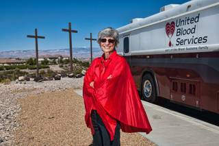 Dressed in a red cape emulating a droplet of blood, GriefShare facilitator Carol Von Eschen stands in front of the United Blood Services' mobile van waiting to greet church members during their blood drive at New Song Church in Henderson Sunday, April 6, 2014.