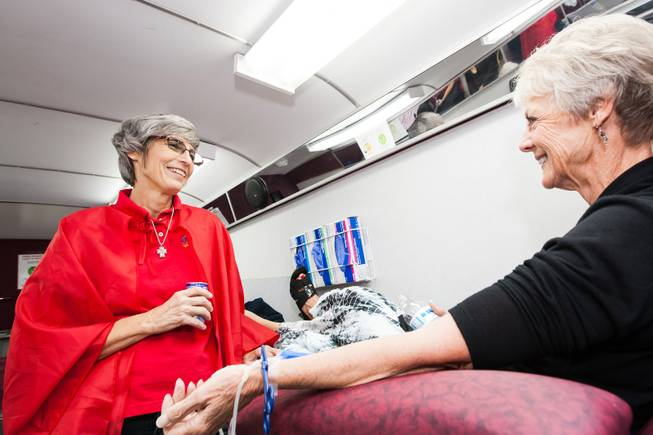 GriefShare facilitator Carol Von Eschen checks on Judy Enerson while she donates blood in the United Blood Services' mobile van during the blood drive at New Song Church in Henderson Sunday, April 6, 2014.