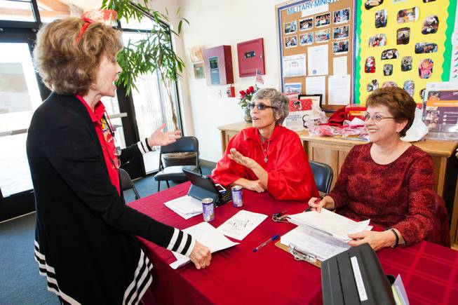 GriefShare facilitator Carol Von Eschen, center, laughs with volunteers Kitty Metzger and Brenda Wendling, right, while working the booth during the blood drive at New Song Church in Henderson Sunday, April 6, 2014.