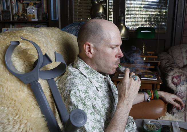 In this April 30, 2014 photo, Bill Britt, 54, who suffers from epileptic seizures and leg pain from a childhood case of polio, vaporizes medical marijuana at his home in Long Beach, Calif.