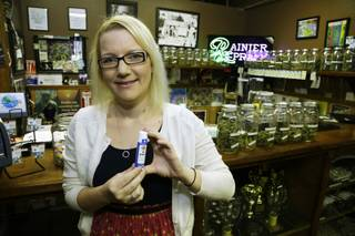 In this photo taken May 2, 2014, Kari Boiter, of Tacoma, Wash., poses for a photo at Rainier Xpress, a medical marijuana dispensary in Olympia, Wash. Boiter has Ehlers-Danlos syndrome, a genetic disorder that causes pain, nausea and vomiting, and says marijuana replaced prescription drugs like steroids and antidepressants what were nearly ineffective for her.