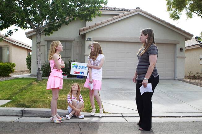 Katelyn, Emily, Danielle and their mother Denzi Watts wait for the start of the presentation of their home which was donated by Bank of America and rehabilitated with the help of Habitat for Humanity Friday, May 9, 2014.
