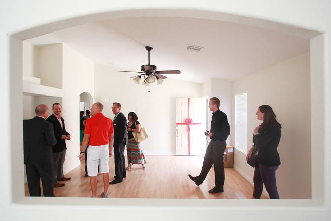 Representatives from Bank of America, Habitat for Humanity and public relations workers mill about after the presentation of a home to Denzi Watts and her three daughters Friday, May 9, 2014.
