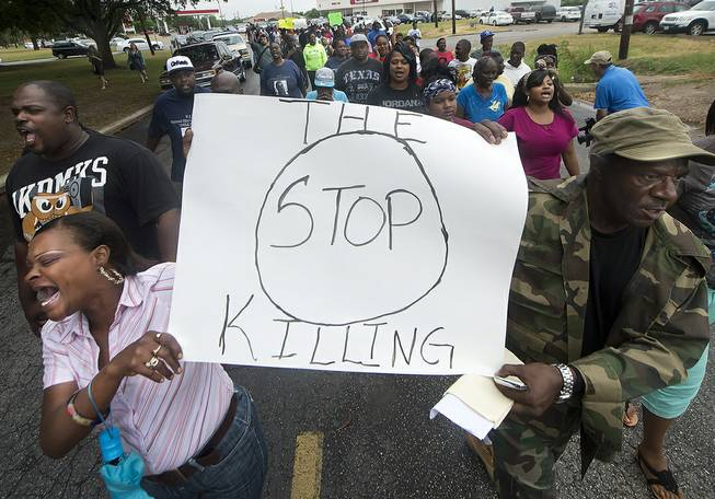 K.K. Davis, left, and Tommy Jones of Hearne carry a sign with other protesters outside the Hearne, Texas police department Thursday, May 8, 2014 following the Tuesday shooting of 93-year-old woman.