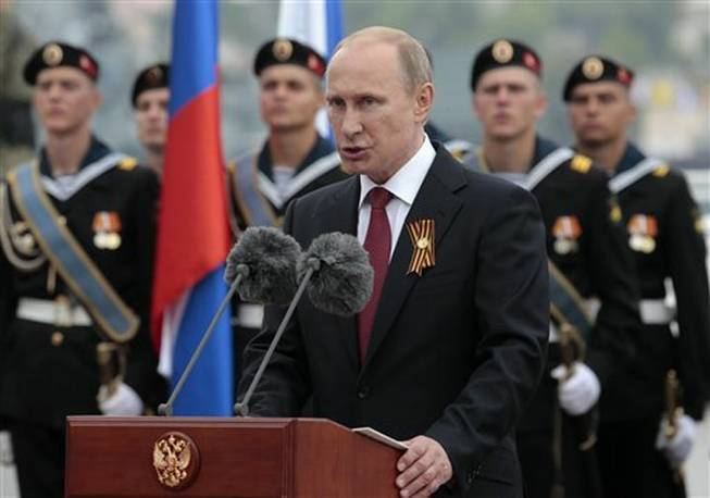 Russian President Vladimir Putin speaks at a navy parade marking the Victory Day in Sevastopol, Crimea, Friday, May 9, 2014.Putin extolled the return of Crimea to Russia before tens of thousands Friday during his first trip to Black Sea peninsula since its annexation. The triumphant visit was quickly condemned by Ukraine and NATO.