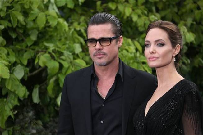 "Actors Brad Pitt and Angelina Jolie arrive for the Maleficent exhibit in Kensington Gardens, London, Thursday, May. 8, 2014. The exhibit showcases some of the costumes and props from the film ""Maleficent,"" before they go on display to the public at the O2 in London."