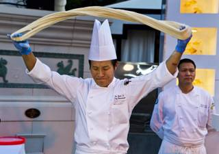 Chef Jin Yuan Li prepares noodles for the crowd at the Grand Tasting during the Uncork'd annual event from Caesars Garden of the Gods Pool on Friday, May 9, 2014.