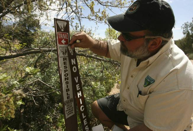 "In this May 6, 2010, photo, Bureau of Land Management's Monticelllo Field Office Manager Tom Heinlein places a BLM ""No Vehicles"" placard at the trail head of Recapture Canyon on the northern outskirts of Blanding, Utah."