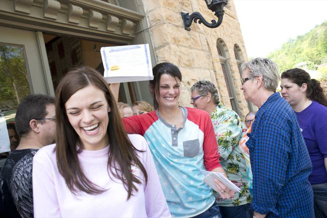 Kristin Seaton, center, of Jacksonville, Ark., holds up her marriage license as she leaves the Carroll County Courthouse in Eureka Springs, Ark., with her partner, Jennifer Rambo, left, of Fort Smith, Ark. Saturday, May 10, 2014, in Eureka Springs, Ark. Rambo and Seaton were the first same-sex couple to be granted a marriage license in Eureka Springs after a judge overturned Amendment 83, which banned same-sex marriage in the state of Arkansas.