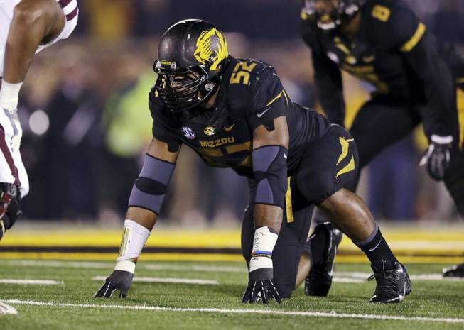 In this Nov. 20, 2013, file photo, Missouri defensive lineman Michael Sam takes up his position during the first half of an NCAA college football game against Texas A&M in Columbia, Mo. Sam was selected in the seventh round, 249th overall, by the St. Louis Rams in the NFL draft Saturday, May 10, 2014.