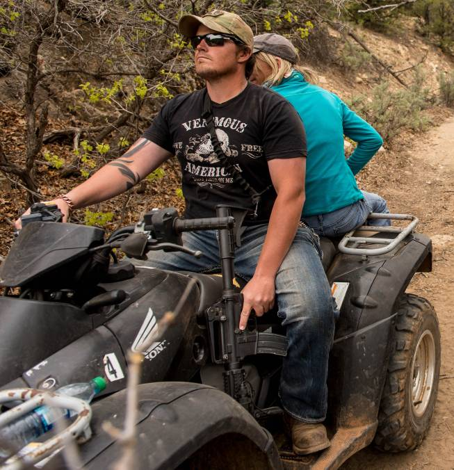 An ATV rider holds his finger near the trigger of his assault rifle as he and others make their way into Recapture Canyon, north of Blanding, Utah, on Saturday, May 10, 2014, in a protest against what demonstrators call the federal government's overreaching control of public lands. The area has been closed to motorized use since 2007 when an illegal trail was found that cuts through Ancestral Puebloan ruins. The canyon is open to hikers and horseback riders.