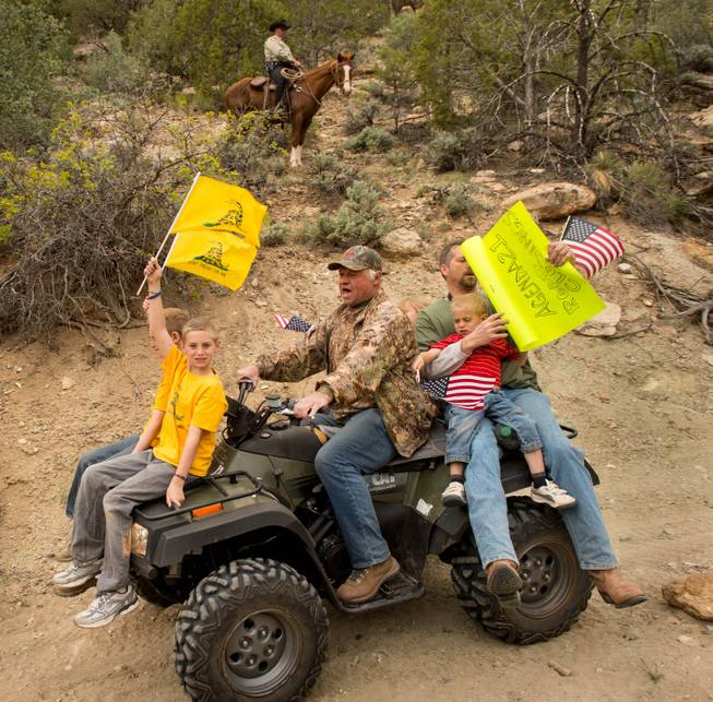 As a Kane County sheriff's deputy watches from a horse, ATV riders make their way into Recapture Canyon, north of Blanding, Utah, on Saturday, May 10, 2014, in a protest against what demonstrators call the federal government's overreaching control of public lands. The area has been closed to motorized use since 2007 when an illegal trail was found that cuts through Ancestral Puebloan ruins. The canyon is open to hikers and horseback riders.