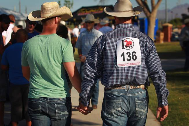 Two cowboys walk hand in hand during the Bighorn Rodeo Saturday, May 10, 2014. The Bighorn Rodeo is an annual event put on by the Nevada Gay Rodeo Association.