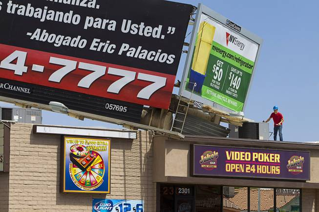 A worker looks over a billboard on the top of Jake's Bar on Eastern Avenue by Sahara Avenue Sunday, May 11, 2014. High winds apparently caused the the billboard to fall on the bar late Saturday night.