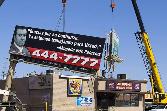 Workers remove a section of a billboard from the top of Jake's Bar on Eastern Avenue by Sahara Avenue Sunday, May 11, 2014. High winds apparently caused the the billboard to fall on the bar late Saturday night.