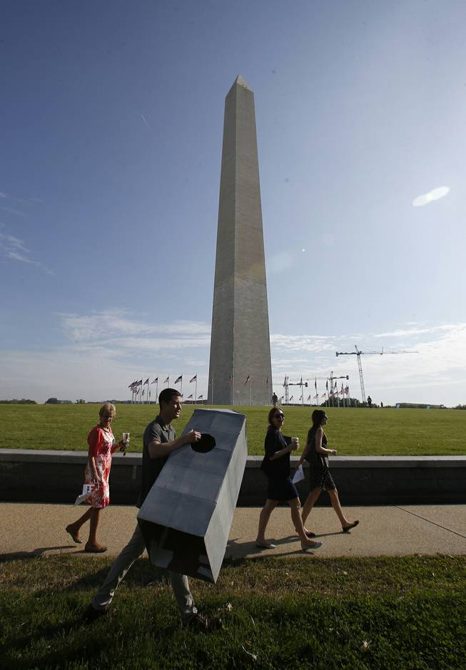 Steven Avila, an Interior Department employee, carries a Washington Monument costume as he arrives at the Washington Monument in Washington, Monday, May 12, 2014, ahead of a ceremony to celebrate its re-opening. The monument, which sustained damage from an earthquake in August 2011, is reopening to the public today. Avila made the costume to show his support for the re-opening of the monument.