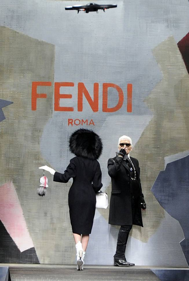 Fashion designer Karl Lagerfeld  is seen at the end of Fendi women's Fall-Winter 2014-15 collection, part of the Milan Fashion Week, unveiled in Milan, Italy, Thursday, Feb.20, 2014. At the top is a drone camera flying over the catwalk.