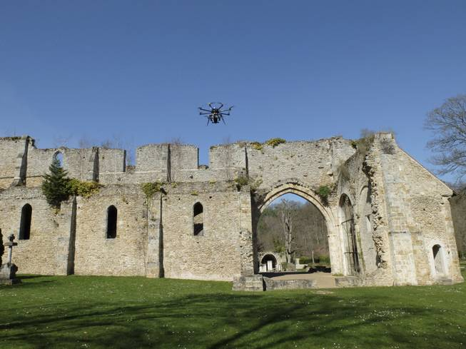 A drone flies at the Abbaye Des-Vaux-de-Cernay southwest of Paris, Thursday March 20, 2014. French drone operator Jean-Luc  Fornier operated the remote controlled drone used to used to transmit live video of snowboard and ski jump competitions at the Sochi Olympic Games.