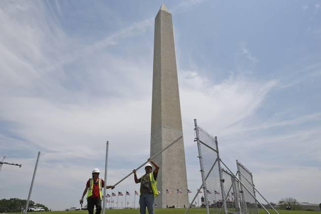 Workers Julio Dichis, right, and Jose Oreyana remove the fencing which closed the Washington Monument off to the public during renovations Washington, Friday, May 9, 2014. The monument, which sustained damage from an earthquake in August 2011, will re-open to the public on Monday, May 12, 2014.