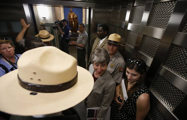 Interior Secretary Sally Jewell, center, rides an elevator to the 500-foot level at the Washington Monument in Washington, Monday, May 12, 2014, after a ceremony to celebrate its re-opening. The monument, which sustained damage from an earthquake in August 2011, reopened to the public today.