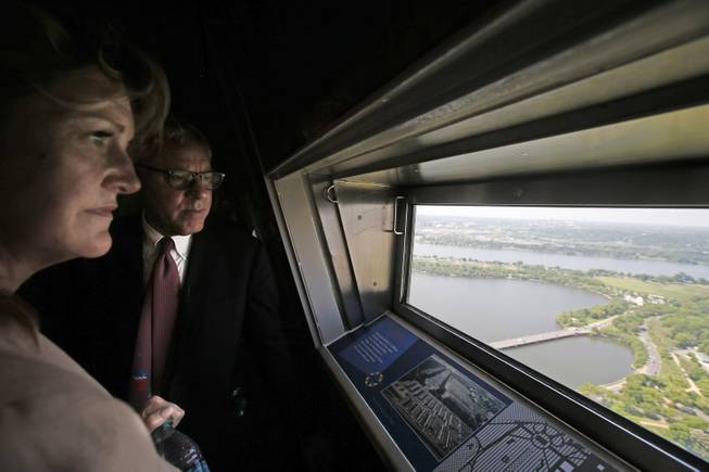 David M. Rubenstein of The Carlyle Group, who partially funded the restoration and Caroline L. Cunningham, take in the view from the 500-foot level at the Washington Monument in Washington, May 12, 2014, after a ceremony to celebrate its re-opening. The monument, which sustained damage from an earthquake in August 2011, reopened to the public today.